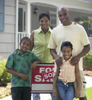 "Family Standing with House's ""For Sale"" Sign"