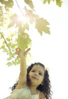 Girl Reaching for a Leaf